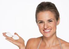 Усмехаясь молодая женщина показывая seashells Стоковая Фотография RF