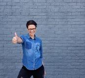 Усмехаясь молодая женщина при стекла показывая большие пальцы руки поднимает знак стоковое изображение rf