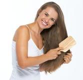 Усмехаясь молодая женщина расчесывая волосы Стоковая Фотография