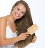Усмехаясь молодая женщина расчесывая волосы Стоковые Фото