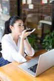 Усмехаясь молодая женщина сидит в кафе Стоковое Изображение