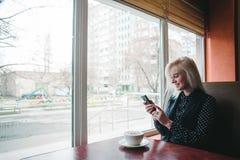 Усмехаясь молодая женщина сидя в кафе около окна с чашкой кофе Стоковая Фотография RF