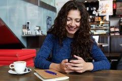 Усмехаясь молодая женщина сидя на кафе используя мобильный телефон Стоковая Фотография