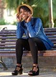 Усмехаясь молодая женщина сидя на скамейке в парке Стоковое Фото