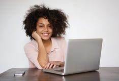 Усмехаясь молодая женщина сидя на таблице с компьтер-книжкой Стоковые Изображения