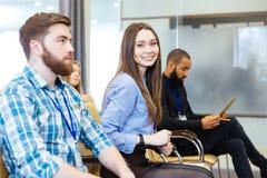 Усмехаясь молодая женщина сидя с коллегами на деловой встрече Стоковые Фотографии RF