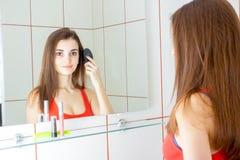 Усмехаясь молодая женщина смотрит в зеркале и расчесывает ее гребень волос Стоковая Фотография RF