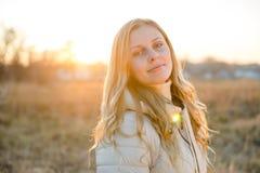 Усмехаясь молодая женщина смотря камеру с голубыми глазами Стоковые Изображения