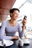 Усмехаясь молодая женщина смотря мобильный телефон на кафе Стоковая Фотография RF