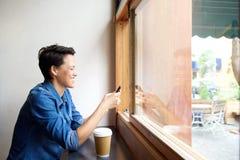 Усмехаясь молодая женщина смотря мобильный телефон Стоковое Изображение RF