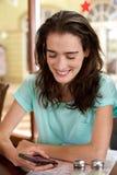 Усмехаясь молодая женщина смотря мобильный телефон Стоковое Фото