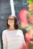 Усмехаясь молодая женщина смотря отсутствующий пока слушая музыка на солнечный день Стоковое Изображение RF