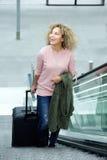 Усмехаясь молодая женщина стоя на эскалаторе с чемоданом Стоковая Фотография RF