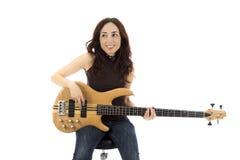 Усмехаясь молодая женщина с басовой гитарой стоковое изображение