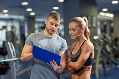 Усмехаясь молодая женщина с личным тренером в спортзале