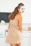 Усмехаясь молодая женщина с косметической маской на стороне в ванной комнате стоковые фотографии rf