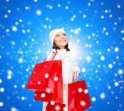Усмехаясь молодая женщина с красными хозяйственными сумками Стоковое фото RF
