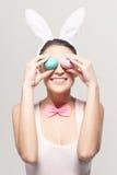 Усмехаясь молодая женщина с красочными пасхальными яйцами Стоковая Фотография RF