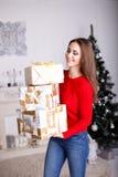 Усмехаясь молодая женщина с подарками и рождественской елкой рождества стоковые фото