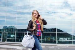 Усмехаясь молодая женщина с сумкой идя и говоря на мобильном телефоне Стоковое Изображение RF