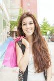 Усмехаясь молодая женщина с хозяйственными сумками в улице Стоковая Фотография