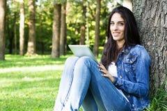 Усмехаясь молодая женщина с цифровой таблеткой стоковое фото