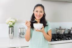 Усмехаясь молодая женщина с шаром салата в кухне Стоковое Изображение RF