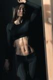 Усмехаясь молодая женщина фитнеса в sportswear представляя с закрытыми глазами Стоковая Фотография