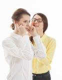 Усмехаясь молодая женщина шепча в ухе коллеги секрету Стоковые Изображения