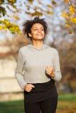 Усмехаясь молодая женщина jogging outdoors в парке Стоковое Изображение RF