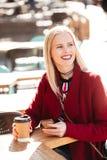 Усмехаясь молодая кавказская женщина сидя в кафе outdoors беседуя Стоковое фото RF