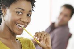 Усмехаясь молодая коммерсантка жуя карандаш Стоковое фото RF