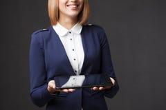 Усмехаясь молодая коммерсантка показывая пустое не-имя tablet монитор ПК с зоной copyspace для лозунга или текстового сообщения c стоковая фотография