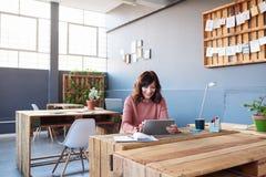 Усмехаясь молодая коммерсантка работая на таблетке в офисе Стоковое фото RF