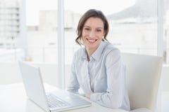 Усмехаясь молодая коммерсантка с компьтер-книжкой в офисе Стоковые Фотографии RF