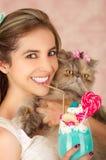 Усмехаясь молодая красивая женщина, носящ смычок волос, держа вкусный голубой молочный коктейль в моде студии, с конфетой сердца Стоковое Изображение