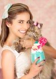 Усмехаясь молодая красивая женщина, носящ смычок волос, держа вкусный голубой молочный коктейль в моде студии, с конфетой сердца Стоковые Фото