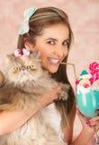 Усмехаясь молодая красивая женщина, носящ смычок волос, держа вкусный голубой молочный коктейль в моде студии, с конфетой сердца Стоковые Изображения RF