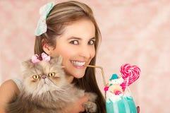Усмехаясь молодая красивая женщина с вкусным голубым молочным коктейлем в моде студии, с конфетой сердца, пластичная солома на a Стоковое Фото