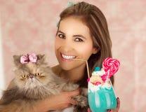 Усмехаясь молодая красивая женщина с вкусным голубым молочным коктейлем в моде студии, с конфетой сердца, пластичная солома на a Стоковые Изображения RF
