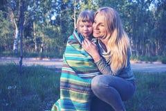 Усмехаясь молодая мать и ее маленькая касающая дочь Стоковые Изображения RF