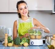 Усмехаясь молодая домохозяйка с брокколи и картошкой Стоковые Изображения RF