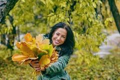 Усмехаясь молодая привлекательная женщина с кленовыми листами осени в парке на падении outdoors Стоковое Фото