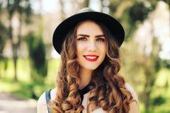 Усмехаясь молодая ультрамодная девушка битника на предпосылке города в солнечном свете внешнем Стоковые Фотографии RF