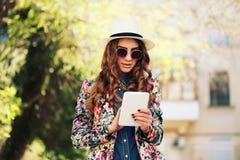Усмехаясь молодая ультрамодная девушка битника на предпосылке города в солнечном свете внешнем Стоковое фото RF