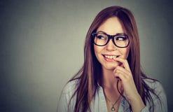 Усмехаясь молодая flirting женщина с пальцем на губах смотря косой Стоковое фото RF