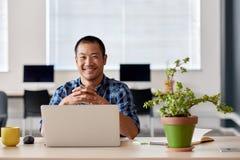Усмехаясь молодой азиатский дизайнер на работе в современном офисе Стоковые Изображения