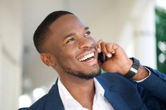 Усмехаясь молодой бизнесмен вызывая мобильным телефоном Стоковое фото RF