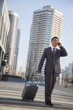 Усмехаясь молодой бизнесмен идя вниз с улицы с багажом и на телефоне стоковые изображения
