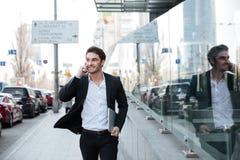 Усмехаясь молодой бизнесмен идя около делового центра Стоковые Изображения